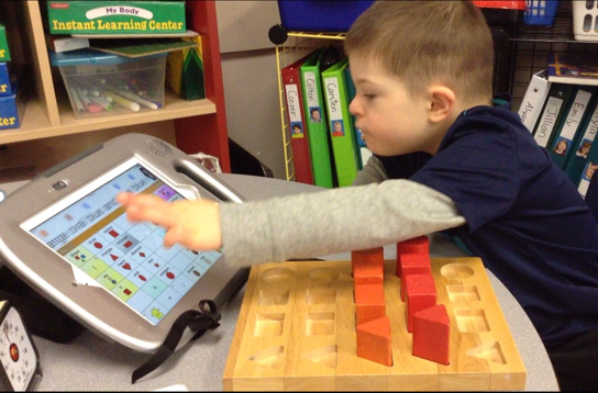 student using a talker and blocks