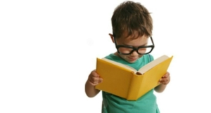 little kid with glasses on reading a book with
