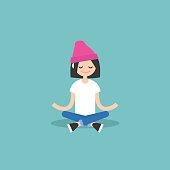 person with a pink hat, sitting cross legged with their palm facing up on their lap