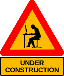 caution triangle sign with a person working on a laptop. words under construction written underneath