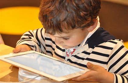 young boy looking at an ipad screen